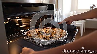 A dona de casa atrativa nova sai da torta quente deliciosa do forno zorra video estoque
