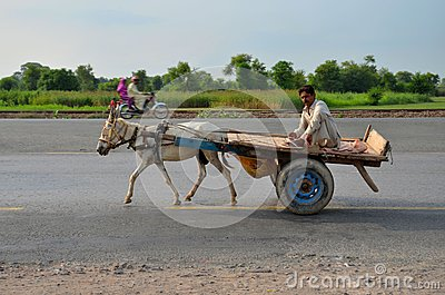 Donkey cart, driver and motorcycle on Pakistan highway Editorial Stock Image
