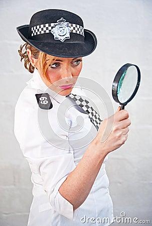 Donna 69 della polizia con la lente d ingrandimento