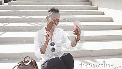 Donna africana che per mezzo dello Smart Phone mentre sedendosi sulle scale bianche all'aperto video d archivio