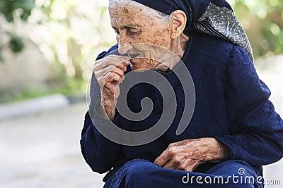 Donna anziana che mangia ciliegia