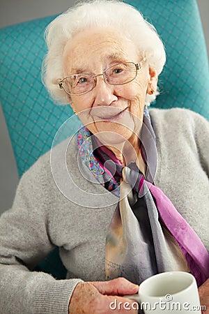 Donna anziana che sembra tè bevente comodo