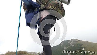 Donna attraente dell'alpinista del vincitore con lo zaino che scala la montagna che incoraggia dopo il raggiungimento del picco d stock footage