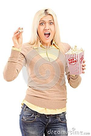 Donna bionda spaventata che tiene un contenitore di popcorn e che grida