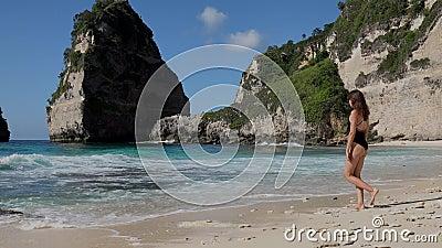 Donna carina che cammina verso l'oceano con rocce di mare e oceano turchese, cielo blu spiaggia di Atuh, isola di Nusa Penida, Ba stock footage