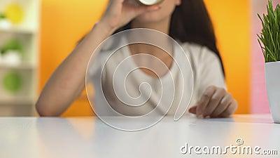 Donna che beve caffè caldo dal vetro della carta e che sorride, energia di mattina, rottura archivi video