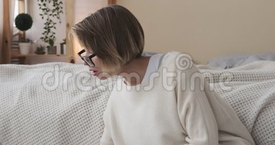 Donna che beve caffè mentre usa un portatile e scrive appunti in camera da letto