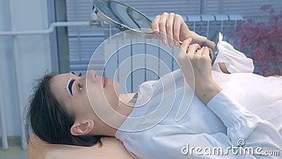 Donna che guarda lo specchio sulla procedura delle sopracciglia di tenda in cosmetologia, vista laterale video d archivio
