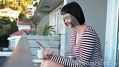 Donna che mangia caffè mentre utilizzando telefono cellulare nel balcone 4k video d archivio