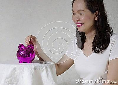 Donna che mette una moneta nel salvadanaio