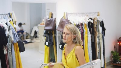 Donna che misura il vestito giallo nel boutique Ragazza alla moda ed alla moda che resta davanti allo specchio Giovani e archivi video