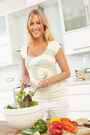Donna che prepara insalata in cucina moderna
