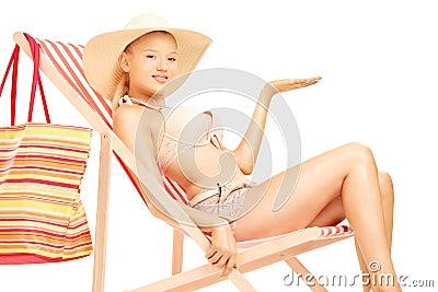 Donna che si siede su una chaise-lounge del sole e che gesturing con una mano