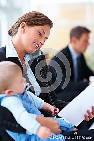 Donna che tiene un bambino e che parla sulla cella