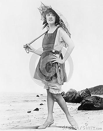Donna con l 39 ombrello ed il costume da bagno di sole alla spiaggia tutte le persone - Il costume da bagno ...