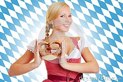 Donna con la ciambellina salata in un dirndl