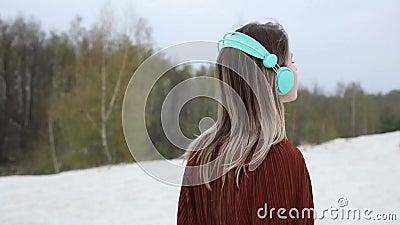 Donna con le cuffie e la blusa di colore di Borgogna sul fondo degli alberi di betulla video d archivio