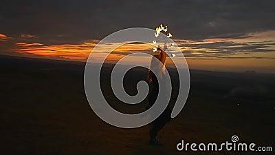Donna con le torce brucianti alla cima della collina stock footage