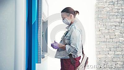 Donna con maschera medica e guanti protettivi di lattice con una bancomat archivi video