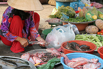 Donna del mercato che prepara i pesci