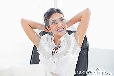 Donna di affari adagiantesi che si siede al suo scrittorio che sorride alla macchina fotografica