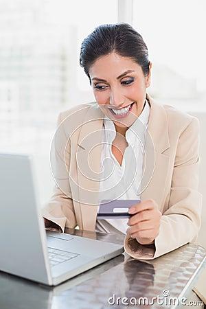 Donna di affari allegra che compera online con il computer portatile