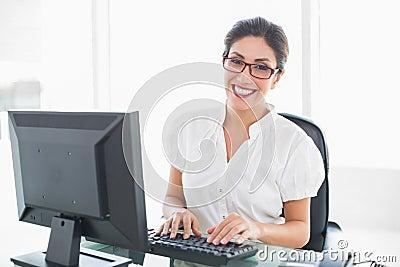 Donna di affari allegra che lavora al suo scrittorio che esamina macchina fotografica