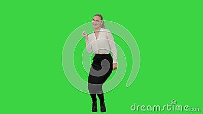 Donna di affari che balla sfrenatamente celebrando riuscito progetto su uno schermo verde, chiave di intensità video d archivio