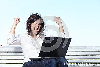 Donna di affari euforica con un computer portatile che si siede su un banco