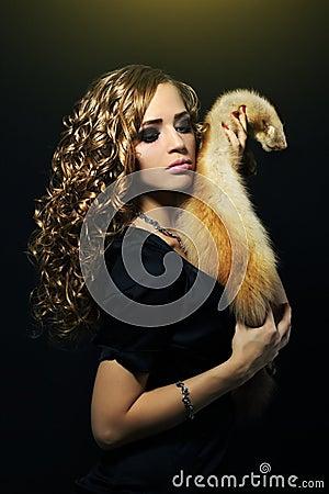 Donna di eleganza che tiene una pelliccia di volpe