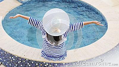 Donna di eleganza di retrovisione dell'angolo alto in cappello con l'arco che si siede sul bordo della piscina o della Jacuzzi stock footage