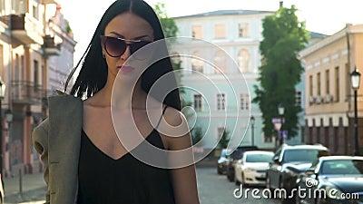 Donna di eleganza in vestiti alla moda ed occhiali da sole che cammina al rallentatore video d archivio