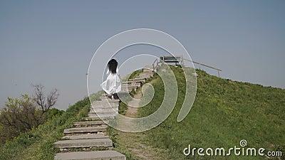 Donna di eleganza in vestito lungo bianco che alza le scale sulla collina verde video d archivio