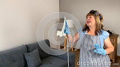 Donna di mezza età, casalinga divertente in grembiule e curatori, che canta e balla con un ferro, un concetto di lavoro domestico archivi video