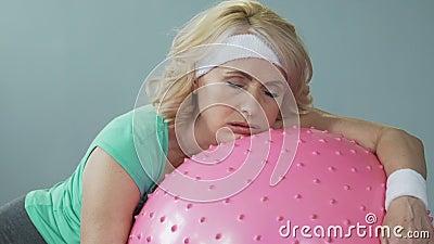 Donna di mezza età stanca sonnolenta che si trova sulla palla di forma fisica dopo l'allenamento attivo archivi video