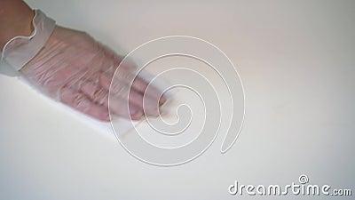 Donna in guanti protettivi pulendo un tavolo bianco con panno video d archivio