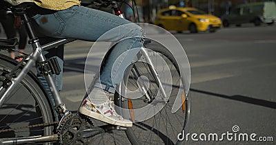 Donna in jeans che aspettano sulla sua bici ad un'intersezione occupata e poi che guidano Movimento lento sparato a Stoccolma archivi video