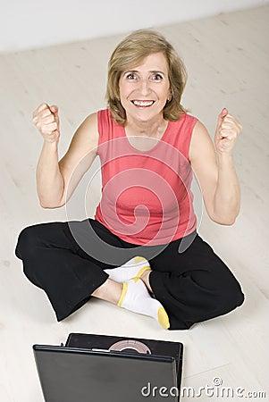 Donna maggiore emozionante con successo sul computer portatile