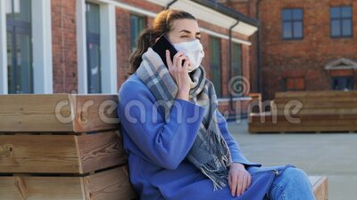 Donna mascherata che chiama smartphone in città stock footage