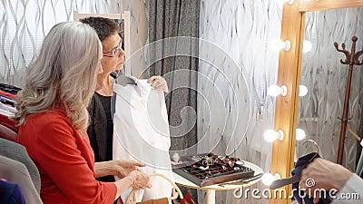Donna matura che sceglie lo specchio anteriore della blusa bianca in sala d'esposizione Stilista di modo che aiuta prova adulta d stock footage