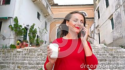 Donna occupata che parla sullo smartphone mentre i funzionamenti si scolano le scale all'aperto archivi video