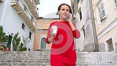 Donna occupata che parla sullo smartphone mentre i funzionamenti si scolano le scale all'aperto video d archivio