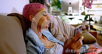 Donna rosa dei capelli che per mezzo del telefono cellulare sul sofà 4k stock footage