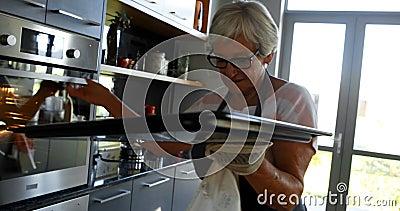 Donna senior che rimuove il vassoio del biscotto dal forno 4k stock footage