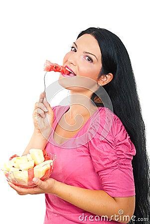 Donna sorridente in buona salute che mangia anguria