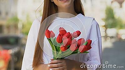 Donna sorridente con la mano tulipana rossa, festa della Giornata internazionale della donna video d archivio
