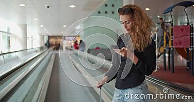 Donna su una scala mobile, con il cellulare e i bagagli all'aeroporto internazionale stock footage