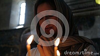 Donna in un foulard che prega in una chiesa cattolica ortodossa stock footage