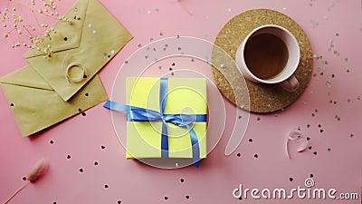 Donne che portano un regalo di Natale avvolto in un foglio giallo con arco blu Vista dall'alto sul tavolo rosa di legno, lastra p archivi video