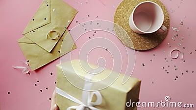 Donne che stringono un regalo di Natale avvolto in un'imbarcazione di carta con un arco bianco Vista dall'alto sul tavolo rosa di archivi video